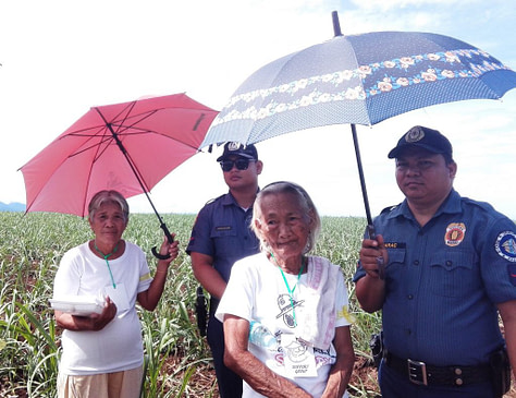 Agrarian Reform Beneficiaries Josefina Carillo and Vicenta Tumampo, assisted by PNP officers, wait for Sheriff Catingub to formally install them in their respective areas.